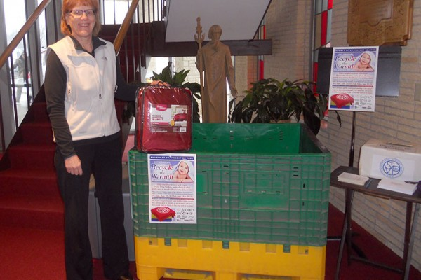 "Karen LaMere, St. Vincent de Paul Society member, in front of the collection barrel in St. Andrew Church for the January ""Recycle the Warmth"" blanket drive which donates bedding to those in need"